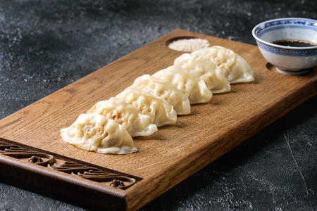 Asian dumplings Gyozas potstickers served with bowl of soy sesame sauce on asian style wooden board over black texture background. Close up.