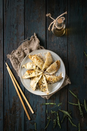 Asian dumplings Gyozas potstickers fried on ceramic plate, served with chopsticks and bottle of sauce over dark wooden plank background. Top view, space. Dark rustic style Stock Photo - 96694033
