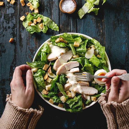 Female hands take by fork Classic Caesar salad with chicken breast in white ceramic plate. Served with ingredients above over old dark blue wooden background. Flat lay. Rustic style. Square image