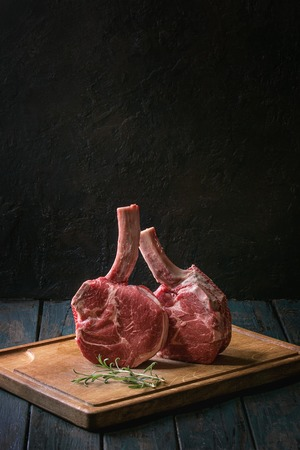 Raw uncooked black angus beef tomahawk steaks on bones served with rosemary, salt and pepper on wooden cutting board over dark wooden plank table. Rustic style. Close up
