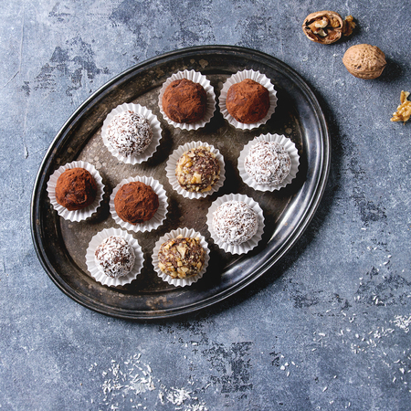 Variety of homemade dark chocolate truffles with cocoa powder, coconut, walnuts on vintage tray over blue texture background. Top view, copy space. Square image