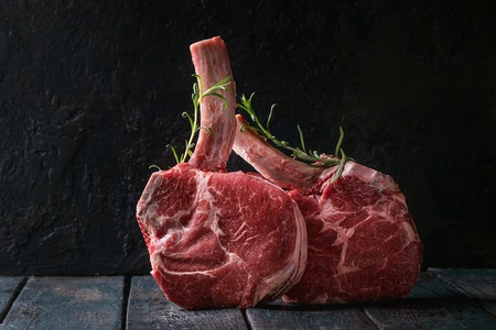 Raw uncooked black angus beef tomahawk steaks on bones served with rosemary over dark wooden plank table. Rustic style. Close up Archivio Fotografico