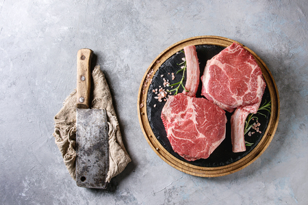 Raw uncooked black angus beef tomahawk steaks on bones served with salt, pepper, vintage butcher cleaver on round wooden slate cutting board over grey texture background. Top view, copy space.