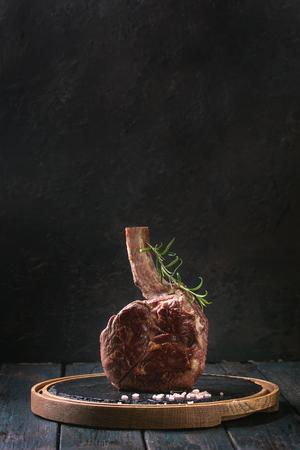 グリルブラックアンガスビーフトマホークステーキは、暗い木製の板のキッチンテーブルの上に丸いスレートのまな板に塩、コショウ、ローズマリーを添えて食べました。スペースをコピーします。 写真素材