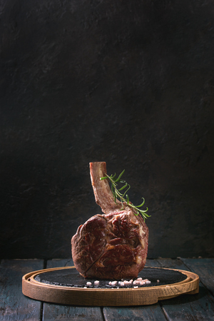 Grilled black angus beef tomahawk steak on bone served with salt, pepper and rosemary on round slate cutting board over dark wooden plank kitchen table. Copy space.