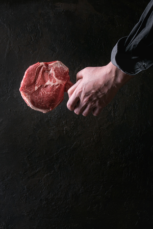 Man's hands holding raw uncooked black angus beef tomahawk steak on bone over dark background. Rustic style Archivio Fotografico - 97295483