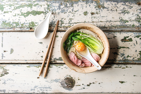 Asian dish udon noodles with egg yolk, sesame, mushrooms, boc choy, sliced sous vide cooked meat served in ceramic bowl with spoon and chopsticks over old white wooden background. Top view, space.