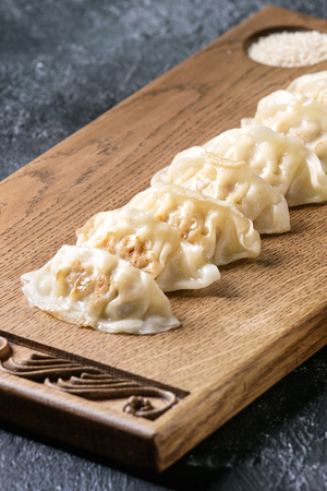 Asian dumplings Gyozas potstickers served with sesame on asian style wooden board over black texture background. Close up. Stock Photo