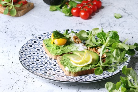 Vegetarian sandwiches with avocado, ricotta, egg yolk, spinach, cherry tomatoes on whole grain toast bread on ceramic plate with ingredients above over white marble kitchen table. Close up