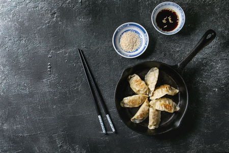 Asian dumplings Gyozas potstickers fried on cast-iron pan, served with chopsticks and bowl of soy sesame sauce over black texture background. Top view, space. Stock Photo