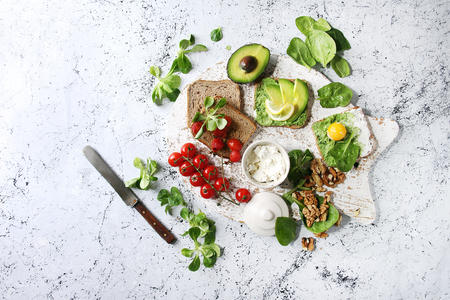 Vegetarian sandwiches with avocado, ricotta, egg yolk, spinach, cherry tomatoes on whole grain toast bread on white serving board with ingredients above over white marble background. Top view, space