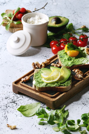 Vegetarian sandwiches with avocado, ricotta, egg yolk, spinach, cherry tomatoes on whole grain toast bread on wooden slate board with ingredients above over white marble background. Close up