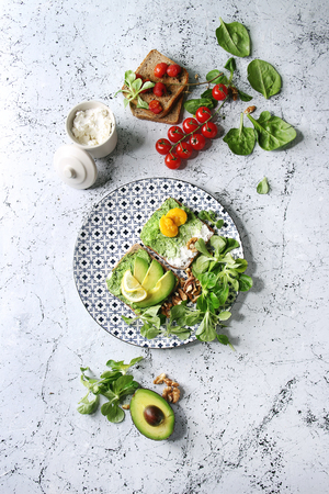 Vegetarian sandwiches with avocado, ricotta, egg yolk, spinach, cherry tomatoes on whole grain toast bread on ceramic plate with ingredients above over white marble background. Top view, space