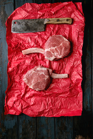 Raw uncooked black angus beef tomahawk steaks on bones served with vintage butcher cleaver on red crumpled paper over dark wooden plank background. Top view, space.