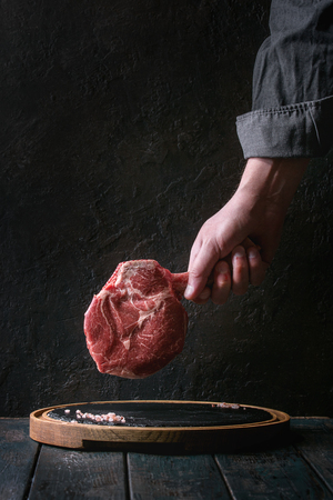 Man's hands holding raw uncooked black angus beef tomahawk steak on bone with salt and pepper on round wooden slate cutting board over dark wooden plank table. Rustic style Archivio Fotografico