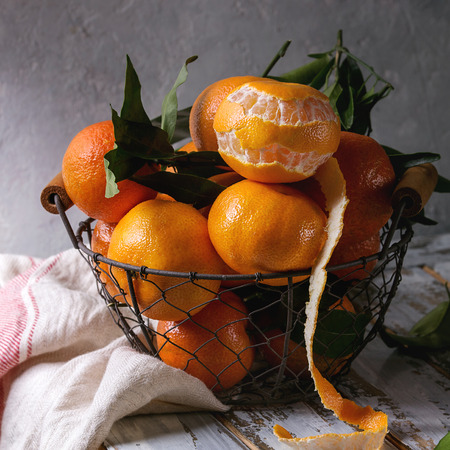 Ripe organic clementines or tangerines with leaves in basket standing with kitchen towel on white wooden plank table with gray wall as background. Rustic style. Healthy eating. Square image