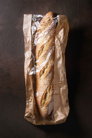 Loaf of fresh baked artisan baguette bread in market paper bag over dark brown texture background. Top view, copy space.