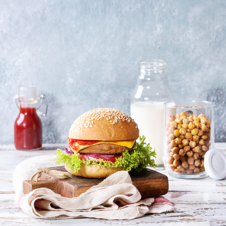 Homemade burger in classic bun with tomato sauce, lettuce, meat, cheese, onion on wood serving board owith bottle of ketchup, milk, roast chickpeas ver white wooden plank table. Square image