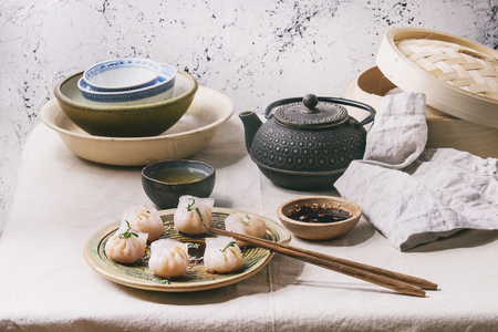 Asian steam potstickers dumplings stuffed by shrimps, served on ceramic plate with soy sesame sauce, chopsticks, teapot, tea, bamboo steamer over kitchen table with linen cloth.