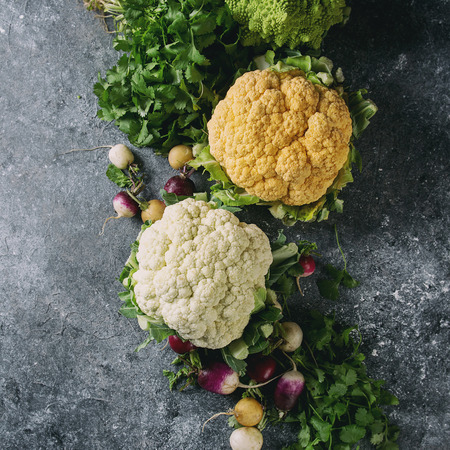 Variety of fresh raw organic colorful cauliflower, cabbage romanesco and radish with bundle of coriander over dark texture background. Top view with space. Healthy eating concept. Square image