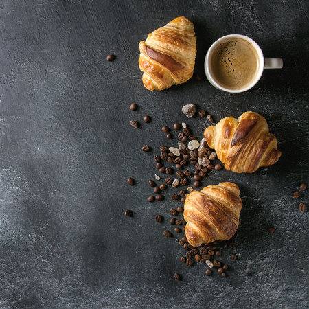 Fresh baked traditional croissants and mug of espresso coffee, coffee beans, sugar over black texture background. Top view, copy space. Square image 写真素材