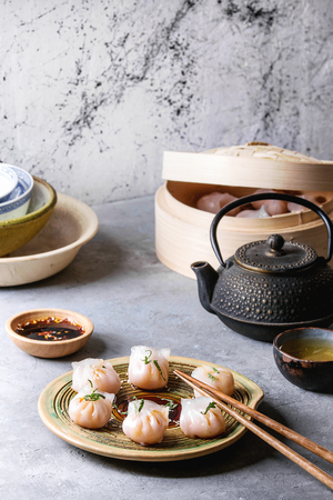Asian steam potstickers dumplings stuffed by shrimps, served on ceramic plate with soy sesame sauce, chopsticks, teapot, tea, bamboo steamer over grey kitchen table. Reklamní fotografie - 98106702