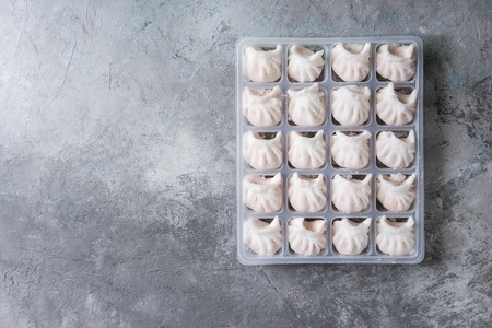 Frozen ready to cook asian potstickers dumplings stuffed by shrimps in plastic box over grey texture background. Top view, space. Semifinished product