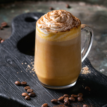Glass of spicy pumpkin latte with whipped cream and cinnamon standing on black serving board. Coffee beans and spices above. Dark background. Square image