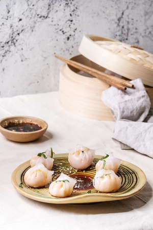Asian steam potstickers dumplings stuffed by shrimps, served on ceramic plate with soy sesame sauce, chopsticks, bamboo steamer over kitchen table with white linen cloth.