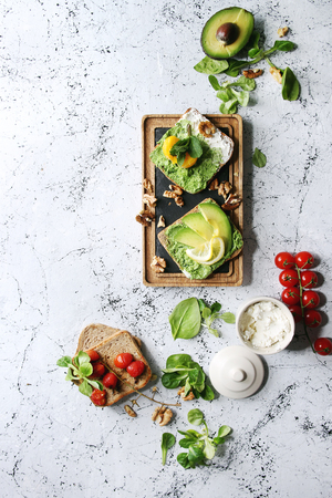 Vegetarian sandwiches with avocado, ricotta, egg yolk, spinach, cherry tomatoes on whole grain toast bread on wooden slate board with ingredients above over white marble background. Top view, space Stock Photo