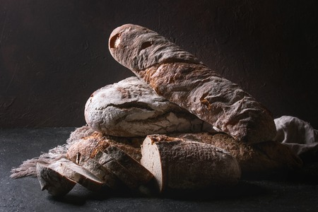 Variety of loafs fresh baked artisan rye and whole grain bread on linen cloth over dark brown texture background. Copy space. Stock Photo