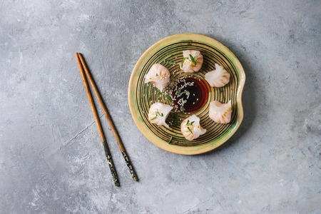 Asian steam potstickers dumplings stuffed by shrimps, served on ceramic plate with soy sesame sauce and chopsticks over grey texture background. Top view, space. Banco de Imagens - 98107035