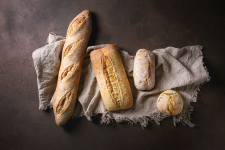Variety of loafs fresh baked artisan white and whole grain bread on linen cloth over dark brown texture background. Top view, copy space. Фото со стока