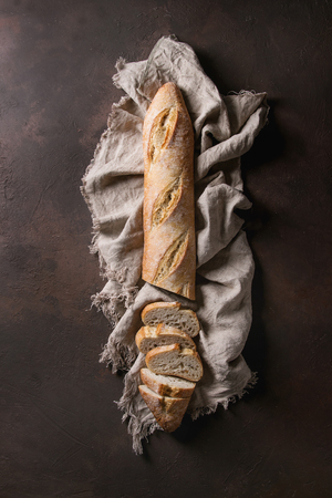 Loaf of sliced fresh baked artisan baguette bread on linen cloth over dark brown texture background. Top view, copy space. Stock Photo - 98107042