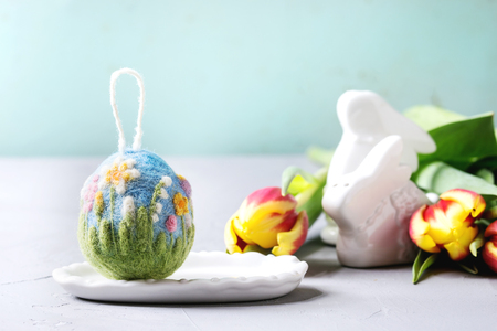 Craft felting Easter egg with blooming flower and green grass decor standing with spring snowdrops bouquet on grey table. Easter decoration and gifts. Copy space