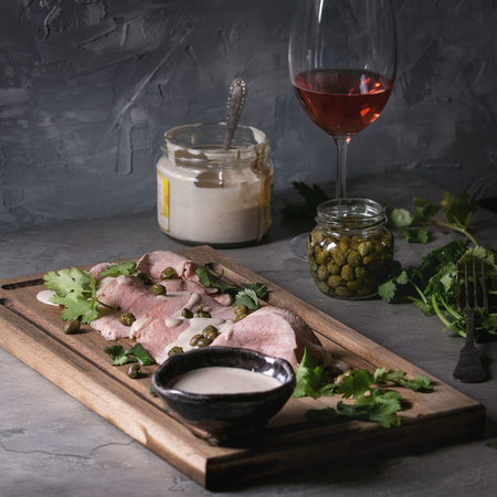 Vitello tonnato italian dish. Thin sliced veal with tuna sauce, capers and coriander served on wooden serving board, glass of rose wine and ingredients above over gray kitchen table. Square image Zdjęcie Seryjne - 98344397
