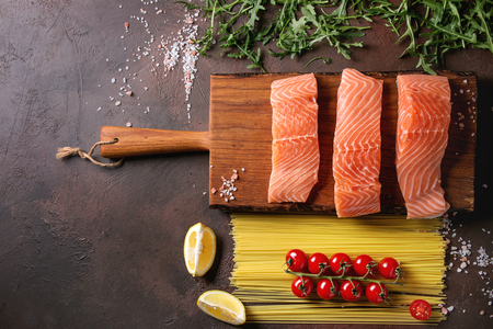 Sliced raw uncooked salmon fillet on wood cutting board with ingredients for dinner, arugula, lemon, salt, pepper, spaghetti pasta, cherry tomatoes over dark brown texture background. Top view, space. Archivio Fotografico - 98344398
