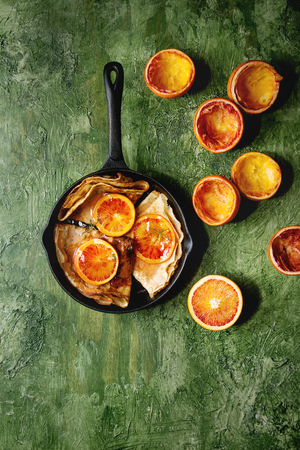 Homemade crepes pancakes served in cast-iron pan with bloody oranges and rosemary syrup with sliced sicilian red oranges over green texture background. Top view, space