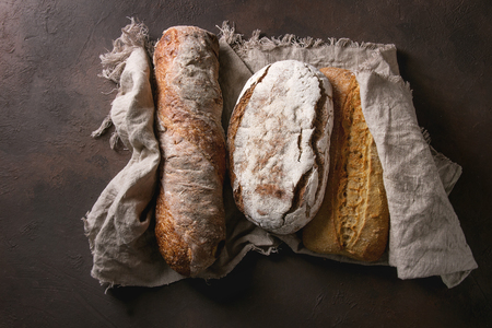 Variety of loafs fresh baked artisan rye, white and whole grain bread on linen cloth over dark brown texture background. Top view, copy space. Stock Photo - 98345264