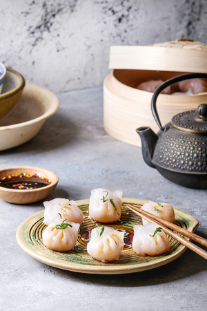 Asian steam potstickers dumplings stuffed by shrimps, served on ceramic plate with soy sesame sauce, chopsticks, teapot, tea, bamboo steamer over grey kitchen table.