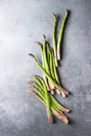 Raw uncooked organic green asparagus in row over grey texture background. Top view, copy space. 版權商用圖片