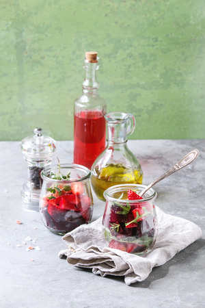 Beetroot and strawberry salad served with arugula and nuts in glass jars with cloth, pepper and bottles of fruit ocet and olive oil over grey table with green wall as background. Healthy eating