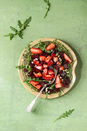 Beetroot and strawberry salad served with arugula and nuts on ceramic plate with fork over green texture background. Top view, space. Healthy eating