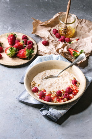 Sweet rice porridge pudding in ceramic plate with berries strawberry and raspberry, walnuts, honey and mug of milk on crumpled paper over grey kitchen table. Stock Photo