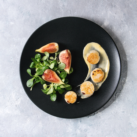 Fried scallops with lemon, figs, sauce and green salad served on black plate over gray texture background. Top view, copy space. Plating, fine dining. Square image