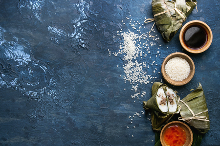 Asian rice piramidal steamed dumplings from rice tapioca flour with meat filling in banana leaves. Ingredients and sauces above over blue texture background. Top view, space. Stock Photo