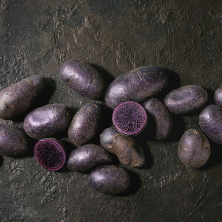 Raw purple uncooked organic potatoes named prunelle, whole and slice over dark texture background. Top view, copy space. Square image Imagens
