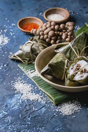Asian rice piramidal steamed dumplings from rice tapioca flour with meat filling in banana leaves served in ceramic bowl. Ingredients and sauces above over blue texture background. Close up, space.