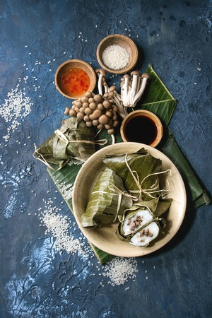 Asian rice piramidal steamed dumplings from rice tapioca flour with meat filling in banana leaves served in ceramic bowl. Ingredients and sauces above over blue texture background. Top view, space. Stock Photo