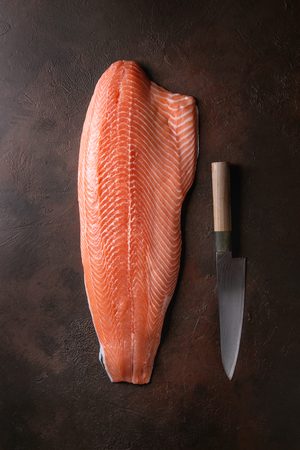 Whole raw uncooked salmon fillet with chef's knife over dark brown texture background. Top view, space.